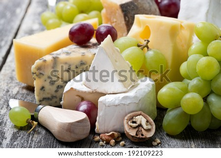 assortment of fresh cheeses and grapes on a wooden background, close-up - stock photo