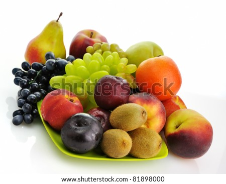 assortment of fresh fruits on a green dish - stock photo