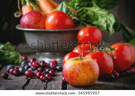 Assortment of fresh fruits, vegetables and berries. Bunch of carrots, spinach, tomatoes and red apples in vintage metal bowl, blueberries and cranberries over old wooden table.  - stock photo