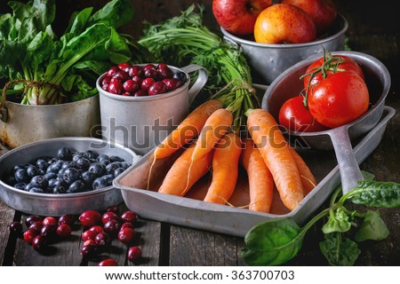 Assortment of fresh fruits, vegetables and berries. Bunch of carrots, spinach, tomatoes and red apples, blueberries and cranberries in vintage aluminum utensil over old wooden table.  - stock photo