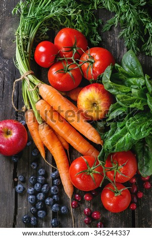 Assortment of fresh fruits, vegetables and berries carrot, spinach, tomatoes, red apples, blueberries and cranberries over old wooden table. Top view - stock photo