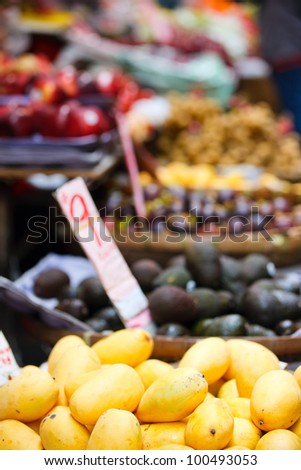 Assortment of fresh mangoes and other fruits on market stall - stock photo