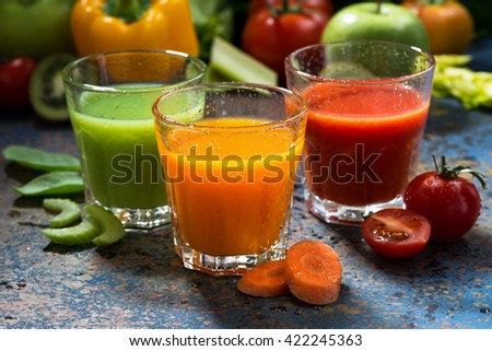 assortment of fresh vegetable juices on a blue background, horizontal - stock photo