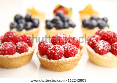Assortment of fruity tarts on white background - stock photo