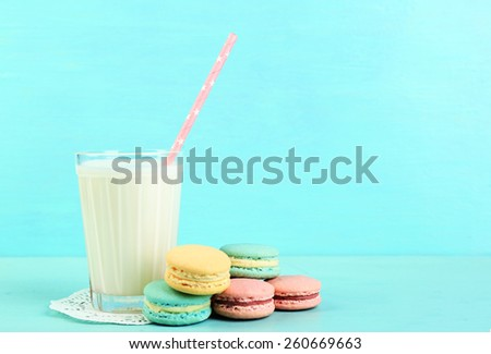 Assortment of gentle colorful macaroons and glass with milk on color wooden background - stock photo
