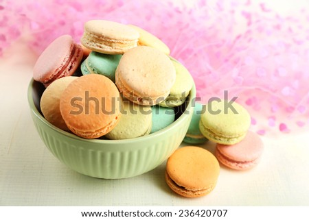 Assortment of gentle colorful macaroons in colorful bowl on color wooden table, on light background - stock photo