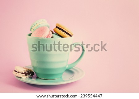 Assortment of gentle colorful macaroons in mug on pink background - stock photo