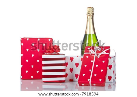 Assortment of gifts and champagne bottle, reflected on white background. Shallow DOF - stock photo
