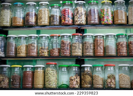 Assortment of glass jars with spices in traditional moroccan pharmacy - stock photo