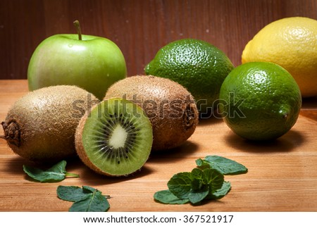 Assortment of green and yellow fruits and vegetables in a wooden rustic environment. Apple, kiwi, lemon, lime and mint leaves are a good source of vitamins and antioxidants - stock photo