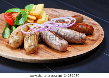 Assortment of grilled sausages on the wooden plate - stock photo