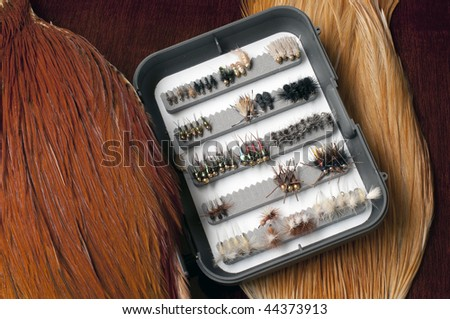 Assortment of hand made trout flies in preparation of fishing trip. - stock photo