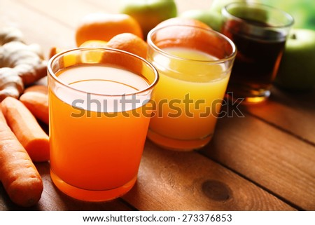 Assortment of healthy fresh juices and fruits on wooden table background - stock photo