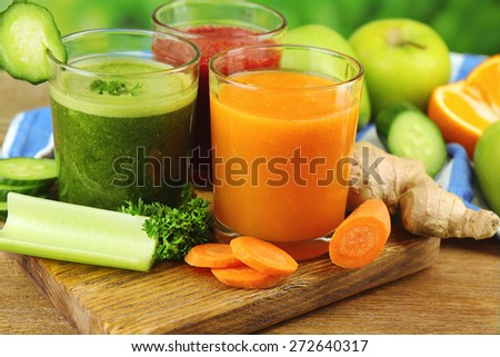 Assortment of healthy fresh juices on wooden table, on bright background - stock photo