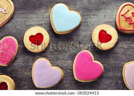 Assortment of love cookies on wooden background - stock photo