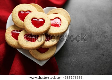 Assortment of love cookies with red cloth on grey background - stock photo