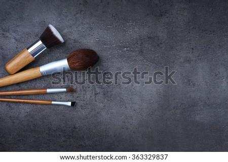 Assortment of make-up brushes, on grey background - stock photo