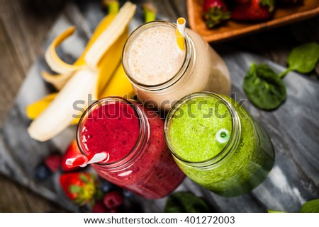 Assortment of milkshakes and smoothies on wooden table - stock photo