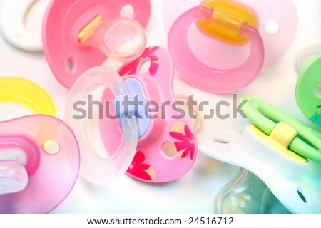 assortment of pacifiers, mostly pink - stock photo