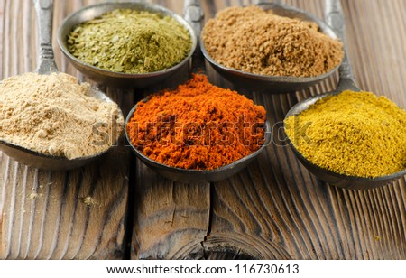 Assortment of powder spices on a wooden table - stock photo