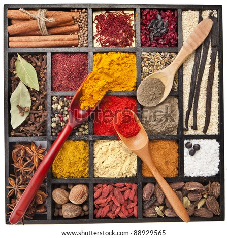 Assortment of powder spices on spoons in wooden box isolated on a white background - stock photo