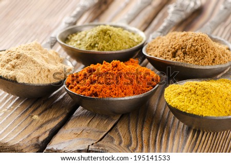 Assortment of powder spices on spoons. Selective focus - stock photo