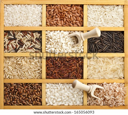 Assortment of rice in wooden box with scoop surface top view - stock photo