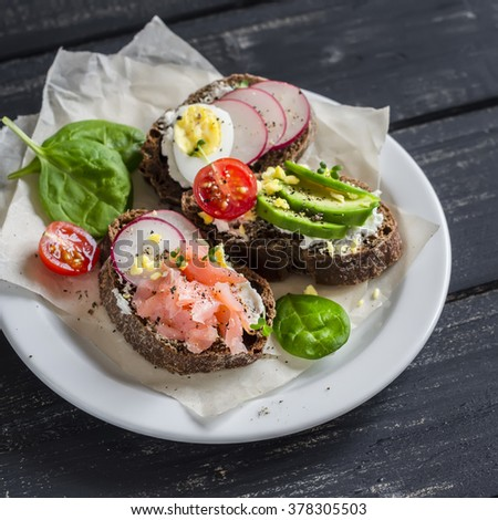 Assortment of sandwiches - sandwiches with cheese, radish,  quail egg, avocado and smoked salmon. Tasty breakfast, snack or appetizer with wine - stock photo