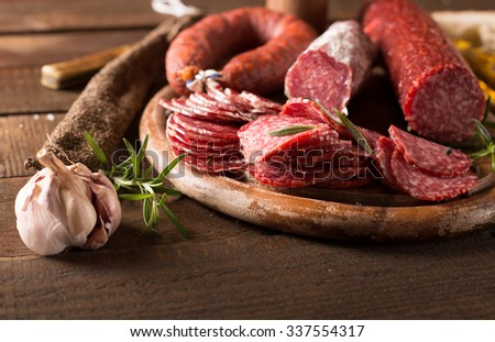 Assortment of sausages on cutting board and wooden table background - stock photo