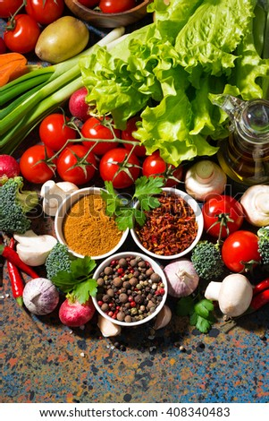 assortment of spices and fresh organic vegetables on a dark background, vertical - stock photo