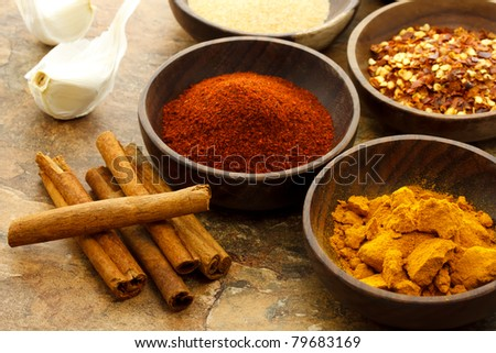 Assortment of spices in wooden bowls - stock photo