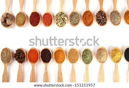 Assortment of spices in wooden spoons, isolated on white - stock photo