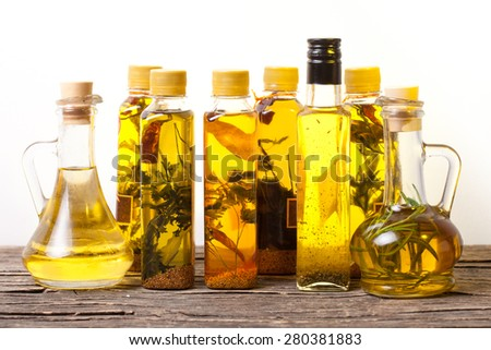 Assortment of spicy oils with herbs and spices in different bottles over white background - stock photo