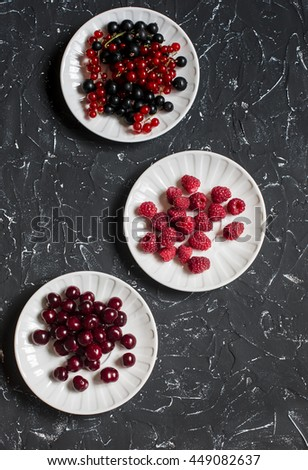 Assortment of summer berries - cherries, raspberries, red and black currant on a dark background - stock photo