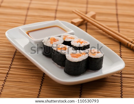 Assortment Of Sushi Rolls Placed On Wooden Mat - stock photo