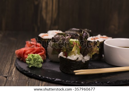Assortment of sushi rolls with salmon and vegetables, served with soy sauce and chopsticks over grunge wooden background. Selective foucs - stock photo