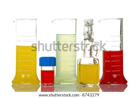 Assortment of test flasks with colored liquids, reflected on white background - stock photo
