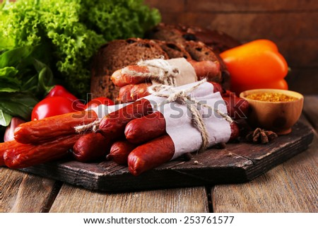 Assortment of thin sausages, bread, mustard in bowl and spices on cutting board, on wooden background - stock photo