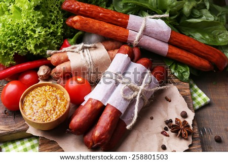 Assortment of thin sausages, mustard in bowl and spices on cutting board, on wooden background - stock photo