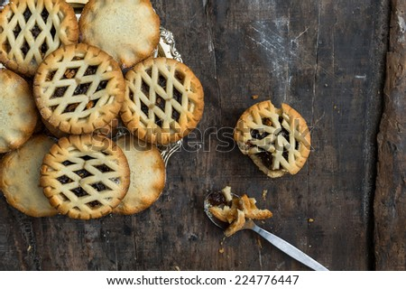Assortment of traditional Christmas mince pies on old rustic wooden table  - stock photo