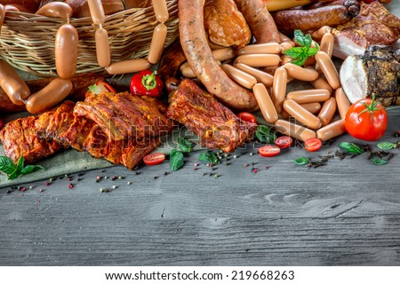 Assortment of various meat and sausages on wooden table - stock photo