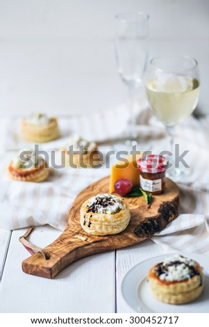 Assortment of various types of appetizers and glass of wine on wooden cutting board - stock photo