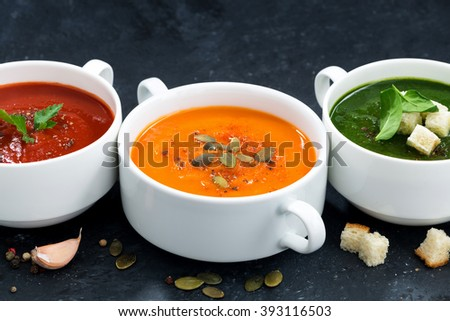assortment of vegetable cream soup on a dark background, closeup, horizontal - stock photo