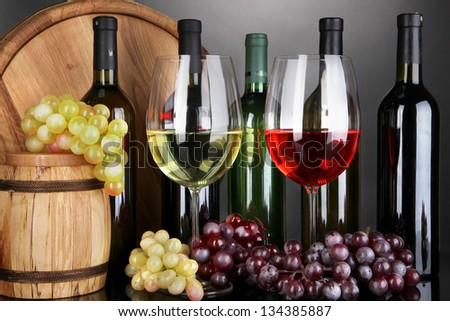 Assortment of wine in glasses and bottles on grey background - stock photo