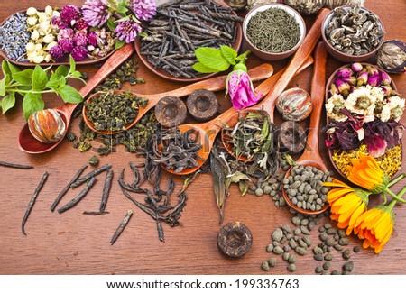assortment variety tea in wooden spoon on kitchen wooden table background - stock photo