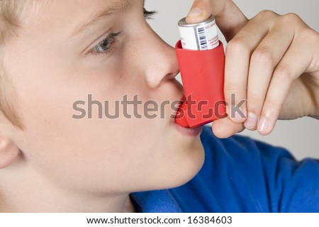 Asthma inhaler being used by boy in blue shirt - stock photo