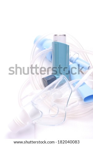 Asthma inhalers with inhalation mask over white - stock photo