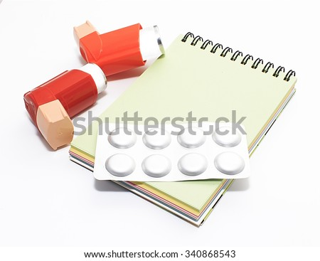 asthma medicine and doctor's prescription. Asthma inhaler, pills and notebook with a blank sheet of paper for your text. Isolated on white background - stock photo