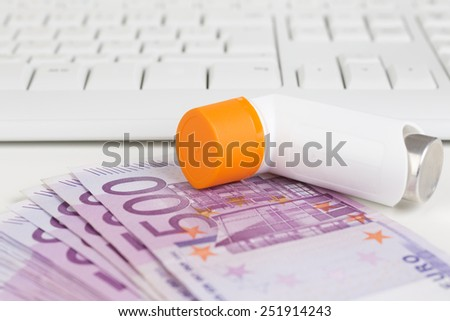 Asthma spray, keyboard and 500 Euro notes - stock photo
