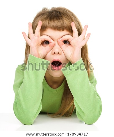 Astonished little girl is showing glasses gesture, isolated over white - stock photo